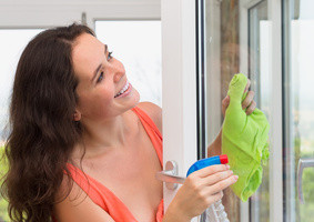 Young wife washing windows in house